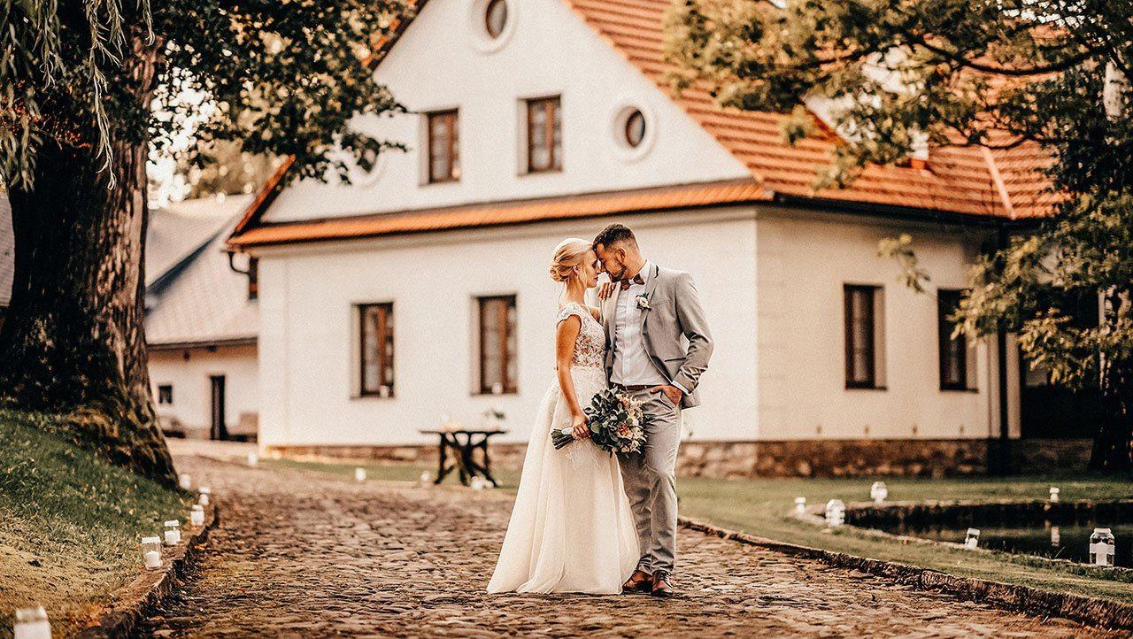 Ženich s nevěstou se k sobě opírají čely v popředí chalupy ve Fojtství Oldřichovice