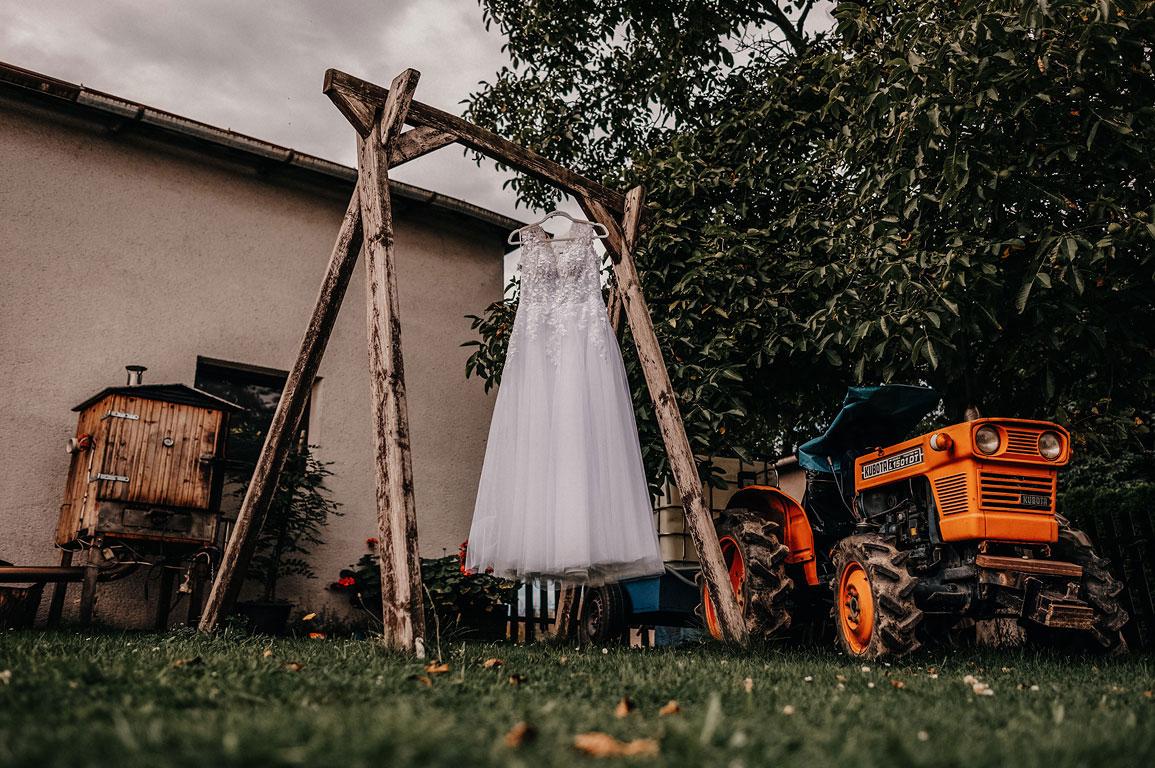 Svatební šaty pověšené na konstrukci pro houpačku. Vedle stojí malotraktor.