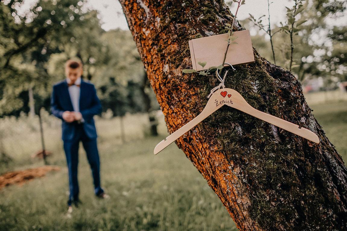 Ramínko s nápisem ženich a srdíčky visící na stromě v pozadí si ženich upravuje sako.