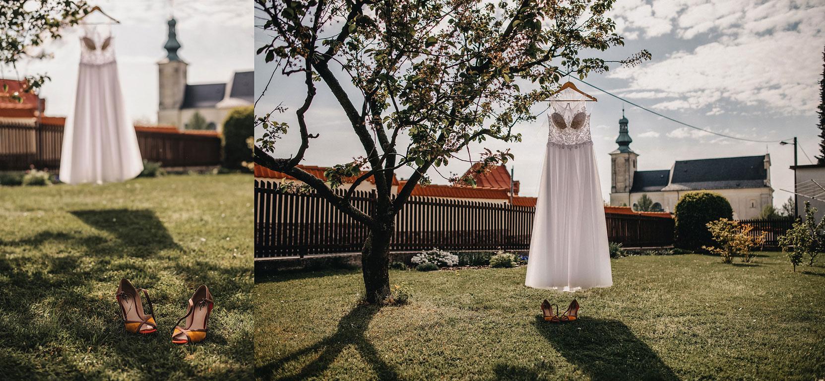Svatební šaty visící na prádelní šňůře. V popředí jsou na trávě boty nevěsty a v pozadí kostel.