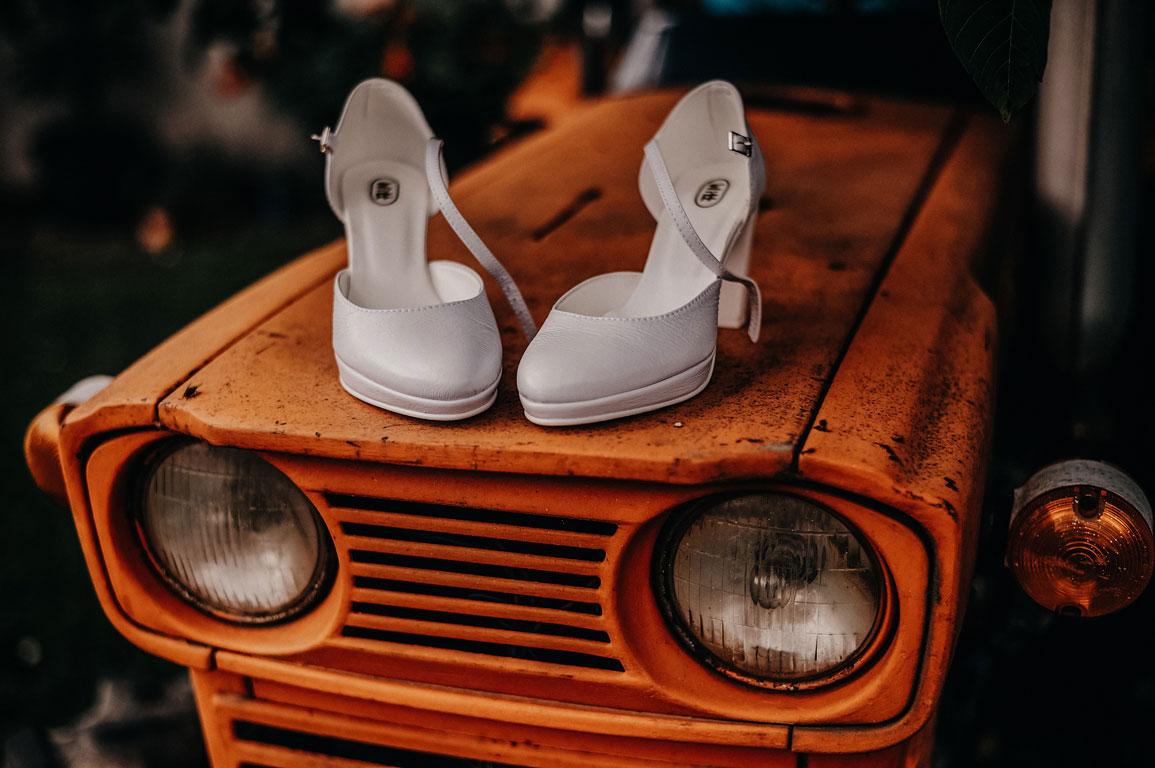 Boty nevěsty ležící na kapotě oranžového malotraktoru