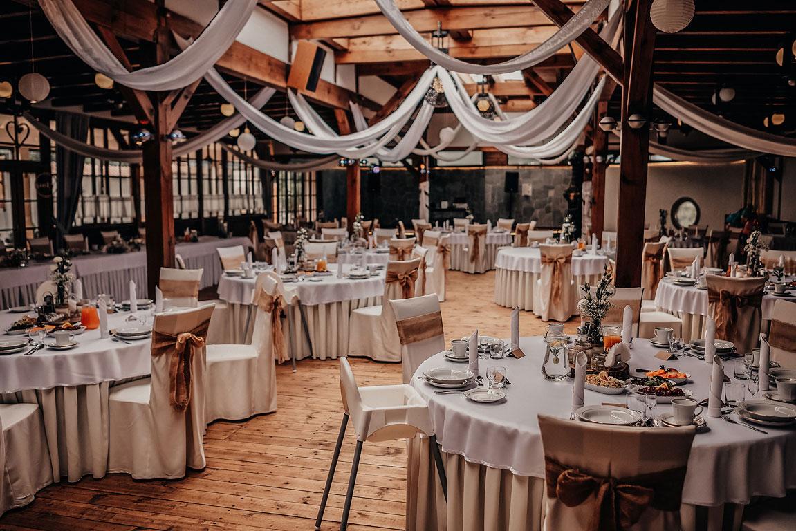 Pohled na prostřené kulaté stoly ke svatební hostině