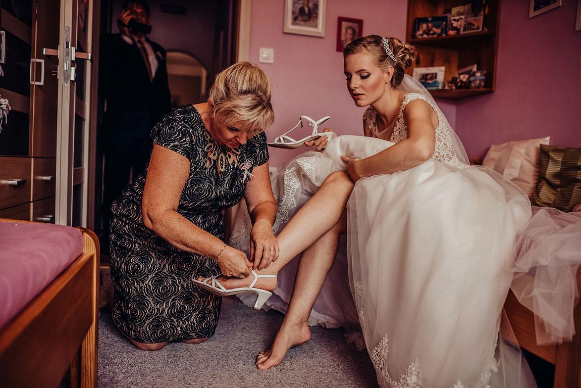 Maminka pomáhá obouvat nevěstě boty