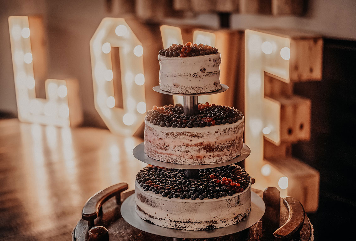 Třípatrový svatební dort s borůvkami a malinami. Na pozadí svítící nápis LOVE
