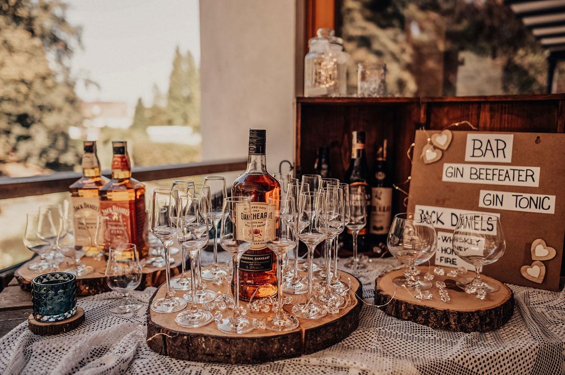 Pohled na pánský koutek s alkoholovými nápoji a skleničkami.