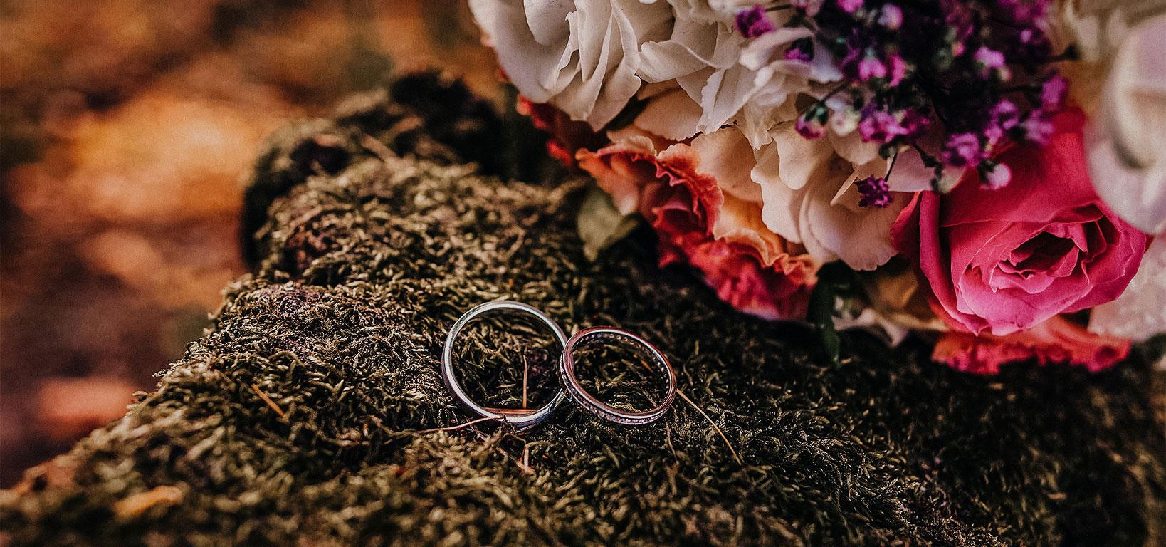 Svatební prstýnky ležící na mechu. V pozadí leží svatební kytice.