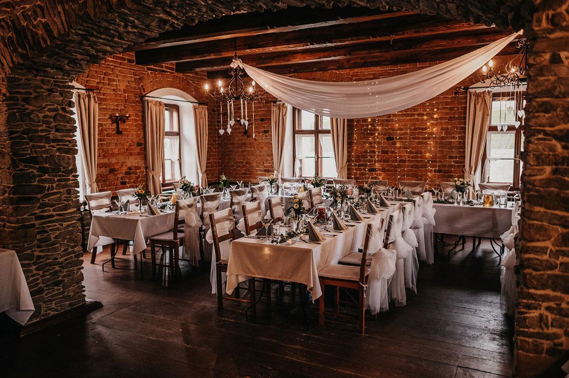 Pohled skrze kameny vyzděný oblouk na prostřené svatební stoly