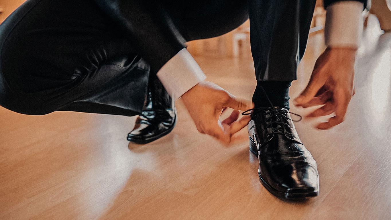 ženich si zavazuje černé svatební boty. Pohybem rozmazané ruce.
