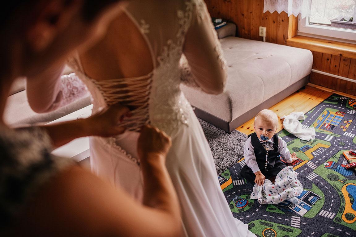 Pohled na sedícího syna nevěsty s dudlíkem. V popředí si obléká nevěsta svatební šaty