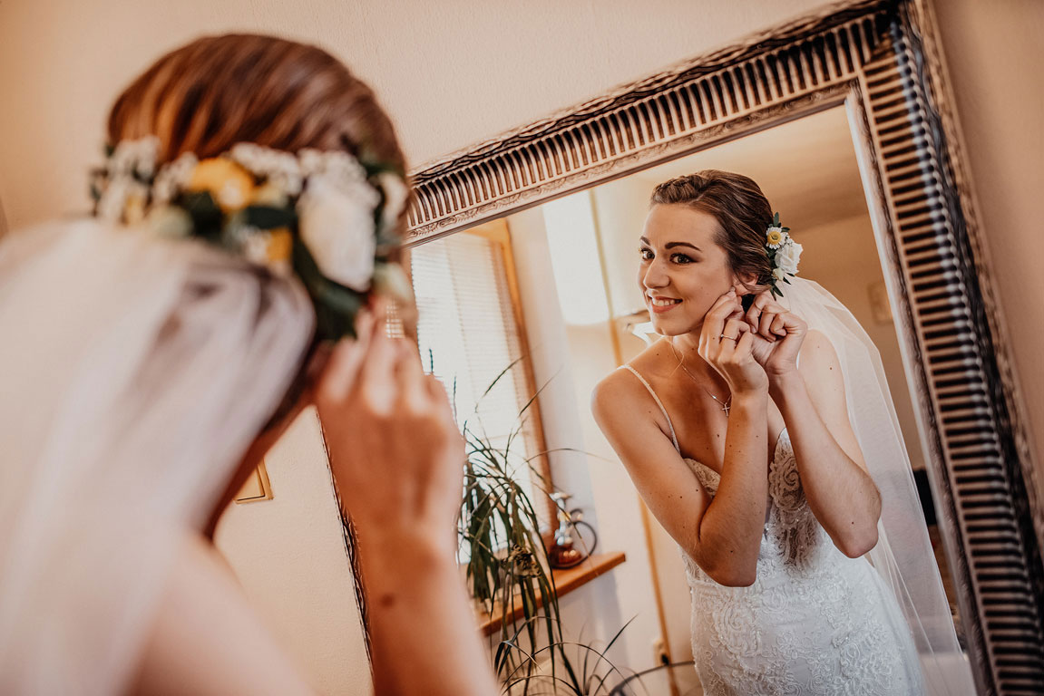Nevěsta si v zrcadle s rámem upravuje náušnice. Ve vlasech má kytky