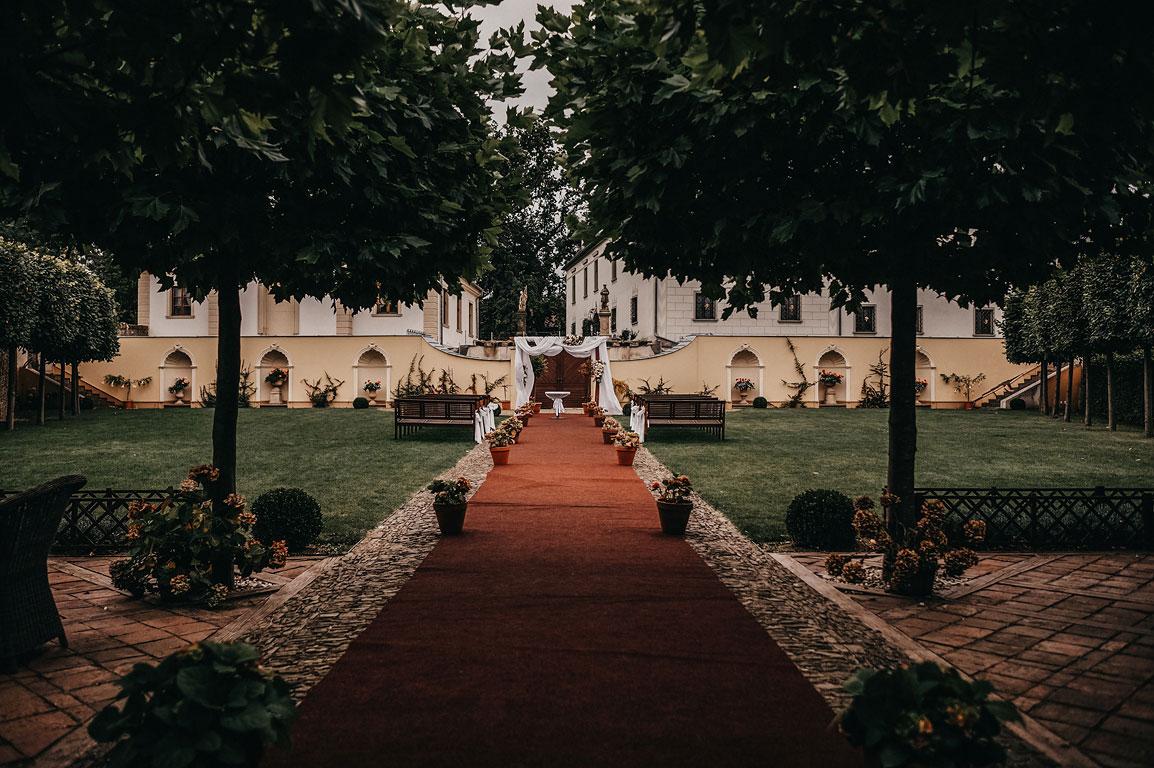 Pohled na vyzdobený svatební oltář připravený k obřadu v zahradě zámku Štáblovice.
