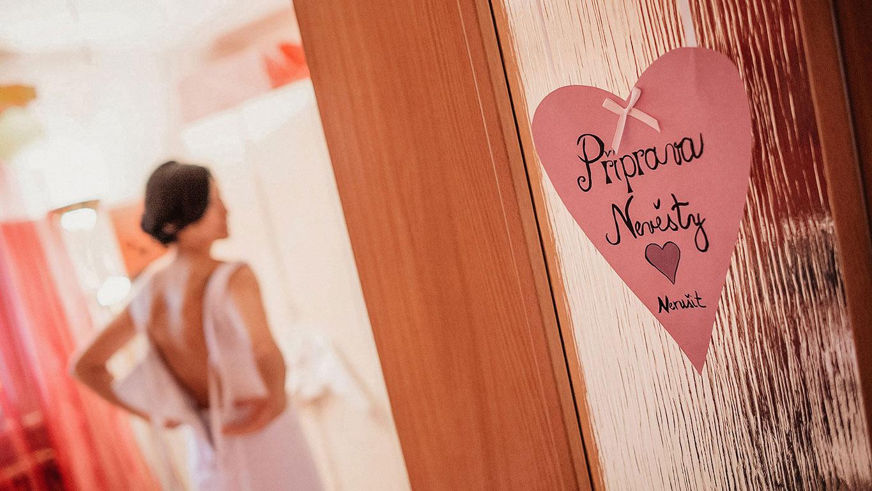 Srdíčko s nápisem příprava nevěsty přilepené na dveřích. V pozdí se obléká nevěsta.