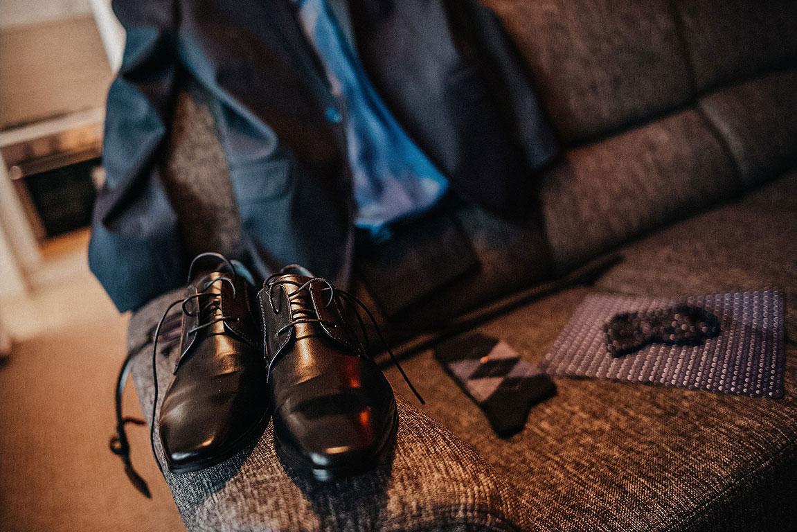 Boty ženicha ležící na opěradle pohovky. V pozadí je opřené sako a ponožky s dalšími doplňky