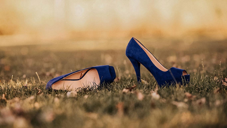 Aranžované modré semišové svatební boty nevěsty v trávě. Jedna naležato, druhá zboku nastojato.