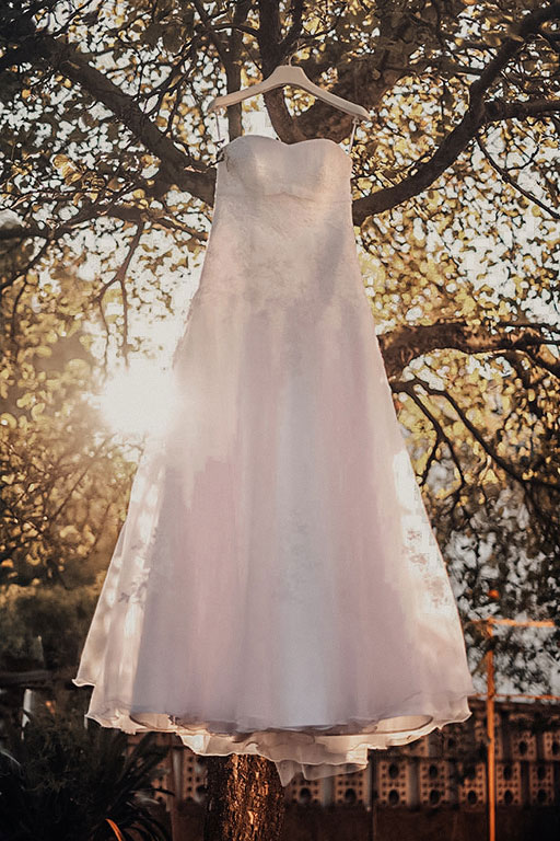 Svatební šaty pověšené na stromě. v pozadí prosvítá přes šaty a větve stromu slunce