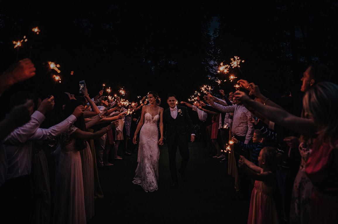 Ženich s nevěstou jdou v noci uličkou mezi lidmi, kteří drží v ruce prskavky