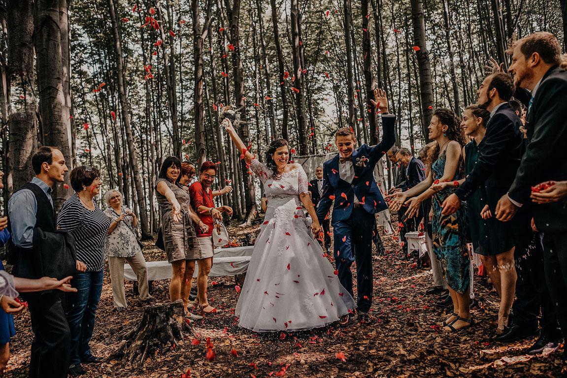 Ženich s nevěstou jdou špalírem v lese mezi lidmi, kteří na ně házejí lístky růže