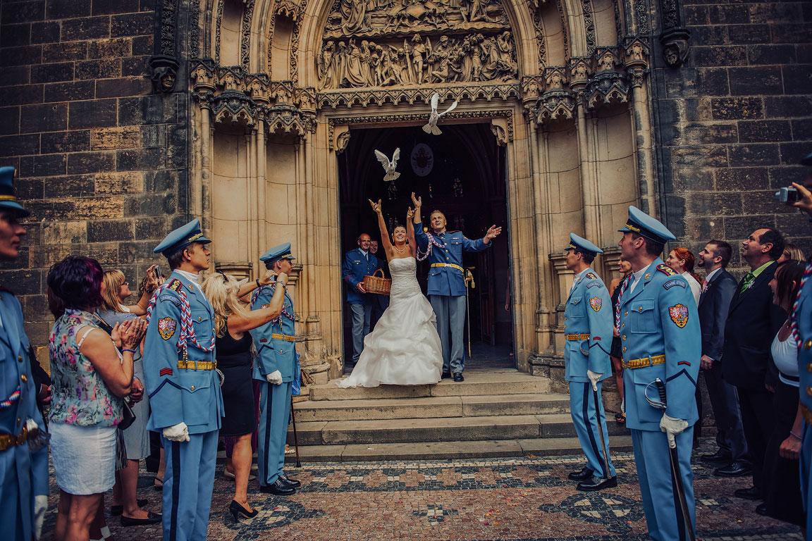 Ženich s nevěstou před vchodem na Vyšehrad vypouštějí holubice. Hradní stráž stojí v pozoru.