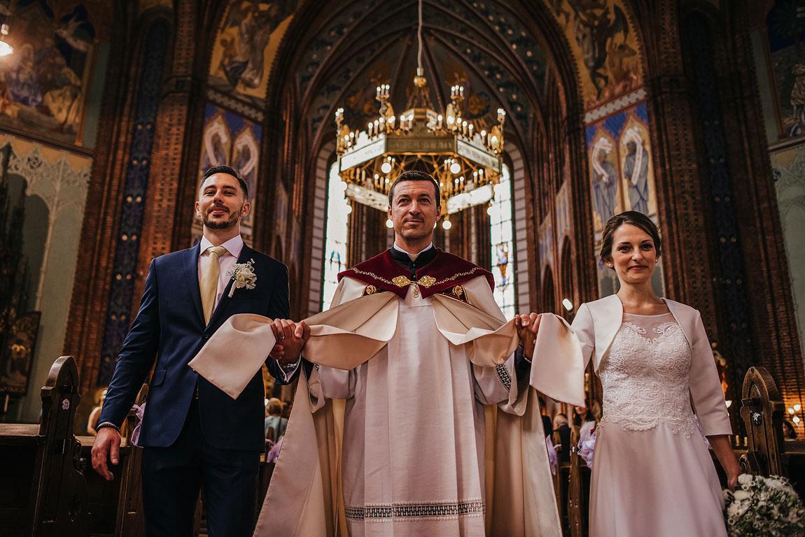 Farář vede za ruce v kostele ženicha a nevěstu. Nad hlavami mají lustr, který vypadá jako koruna