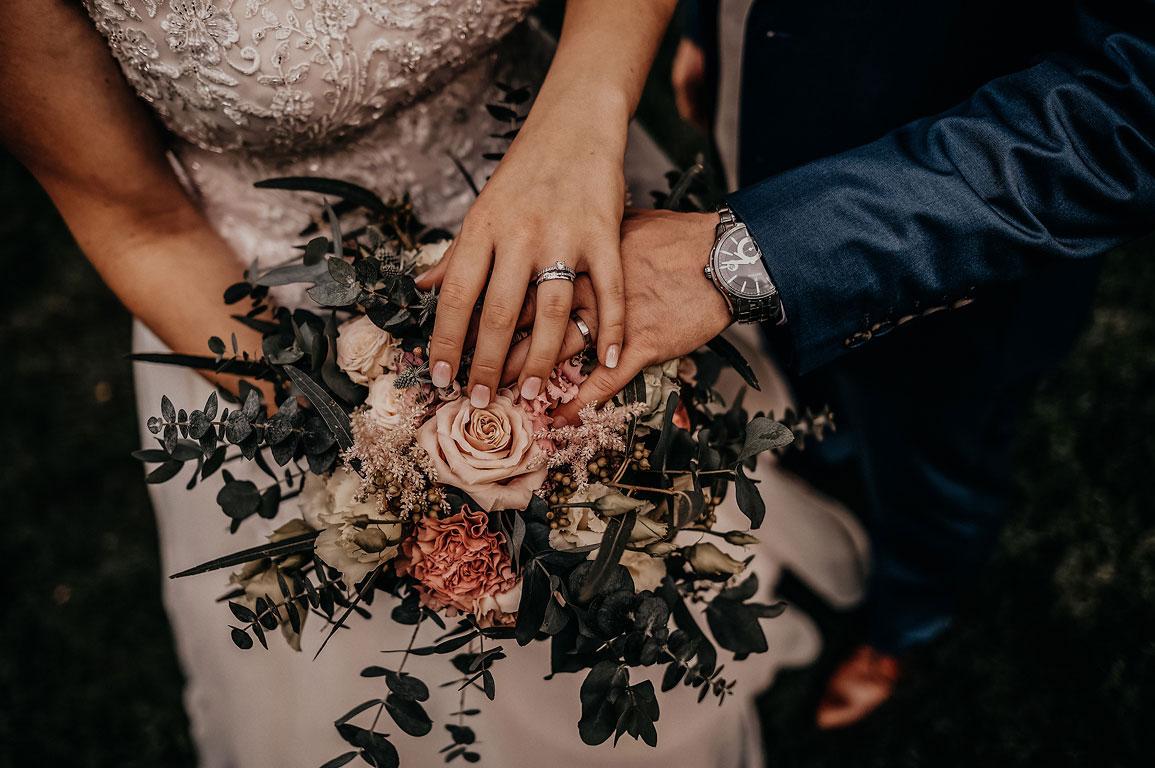 Ruce ženicha a nevěsty položené na kytici, aby šly vidět prsteny