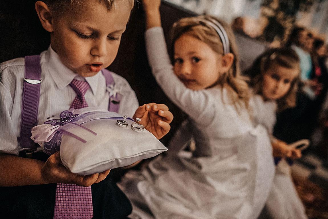 Malý kluk si hraje v kostele se snubními prstýnky položenými na polštáři. V pozadí je malá holka.