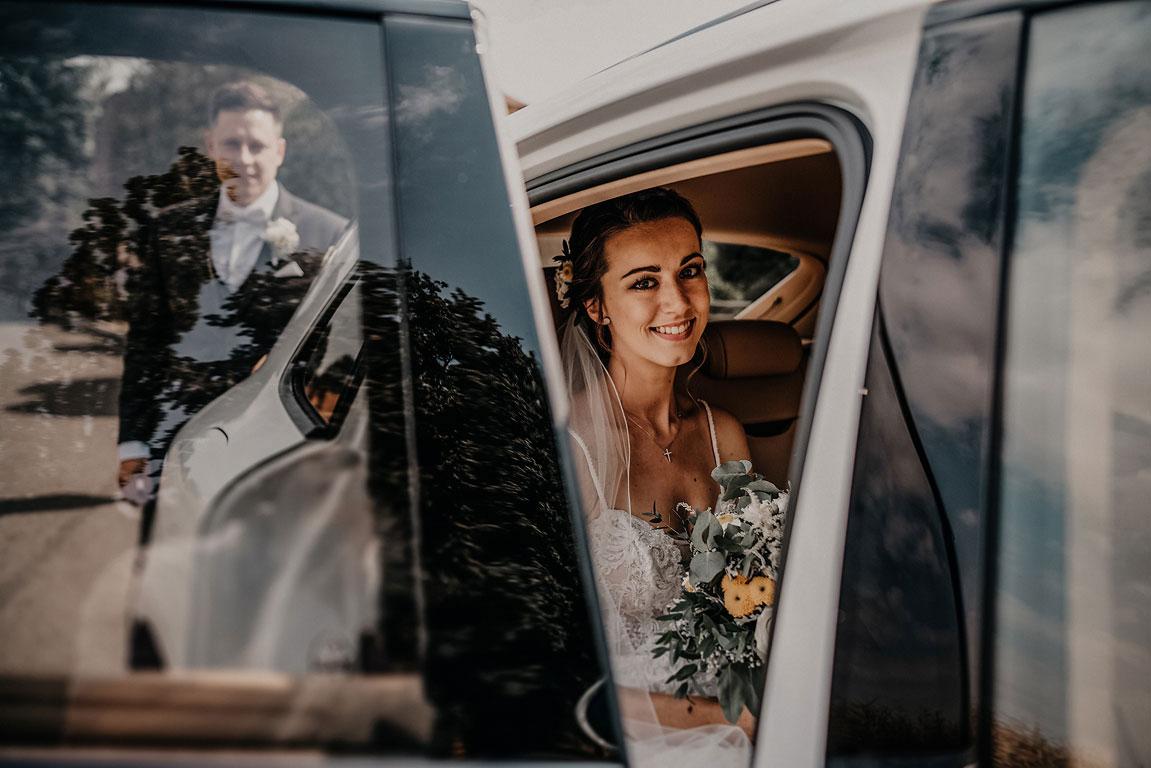Pohled přes otevřené dveře auta na usměvavou nevěstu. V odraze skla je vidět ženich.
