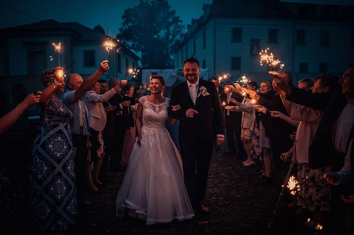 Ženich s nevěstou jdou v noci s úsměvem za ruce uličkou lidí, kteří drží v ruce prskavky.