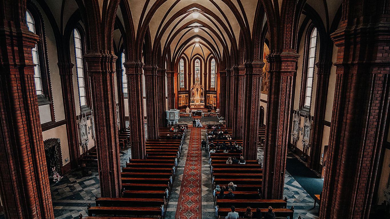 Širokoúhlý pohled na vnitřní prostory kostela, kde před oltářem stojí ženich s nevěstou