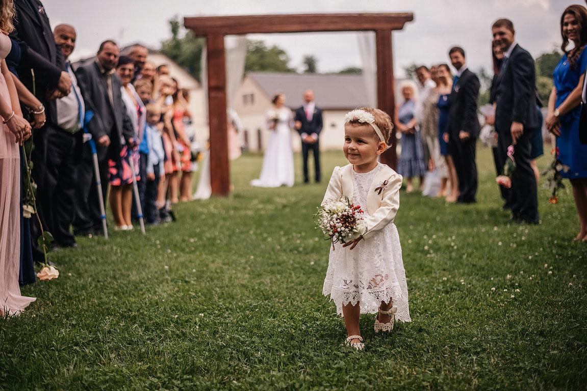malá svatební družička s kytici jde před ženichem a nevěstou