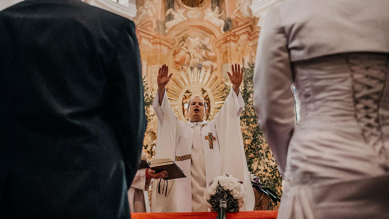 Pohled mezi ženichem a nevěstou na faráře, který jim žehná v kostele s rukama nahoře