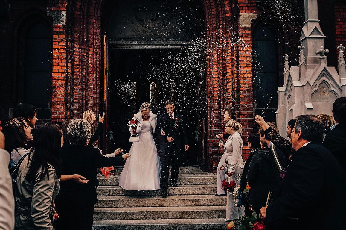Ženich s nevěstou vychází z kostela a lidé na ně házejí rýži