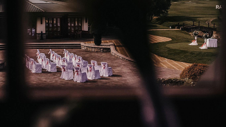 Pohled skrze okno na ozdobené židle a oltář připravený ke svatebnímu obřadu v Golf resortu Čeladná