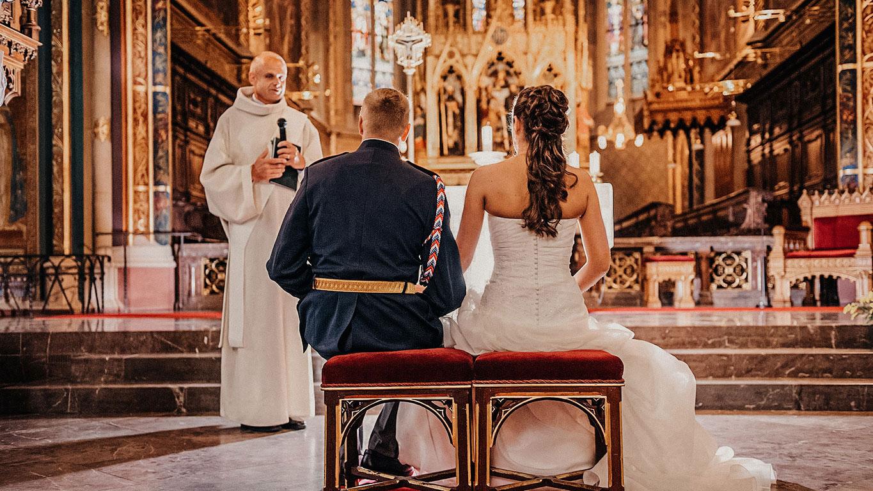 Ženich v uniformě hradní stráže a nevěsta poslouchají faráře na Vysšehradě