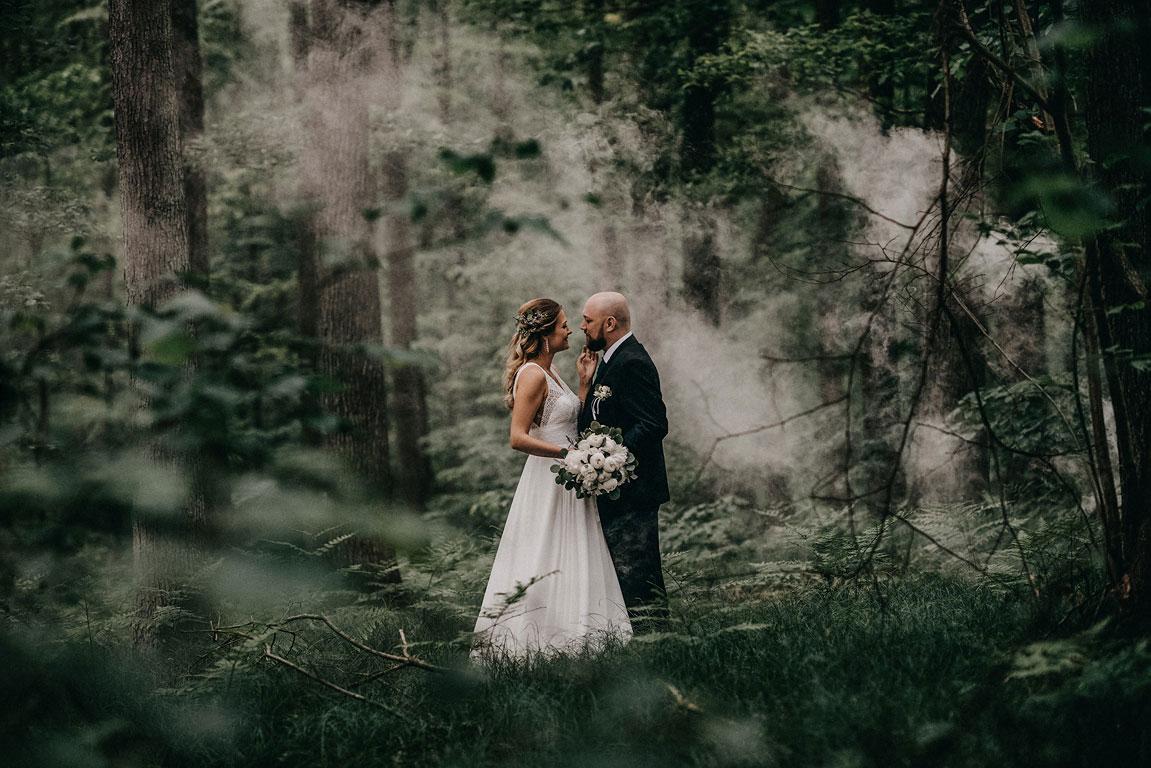 Nevěsta s ženichem stojí k sobě čelem v lese. Nevěst hladí ženicha po tváři a kolem je mlha.
