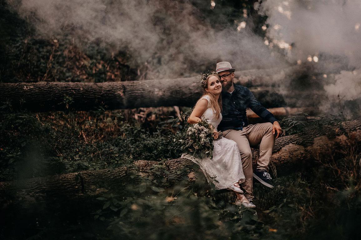 Ženich v klobouku s nevěstou sedí v obětí v lese na kládě. Kolem nich je mlha. Boho svatba.