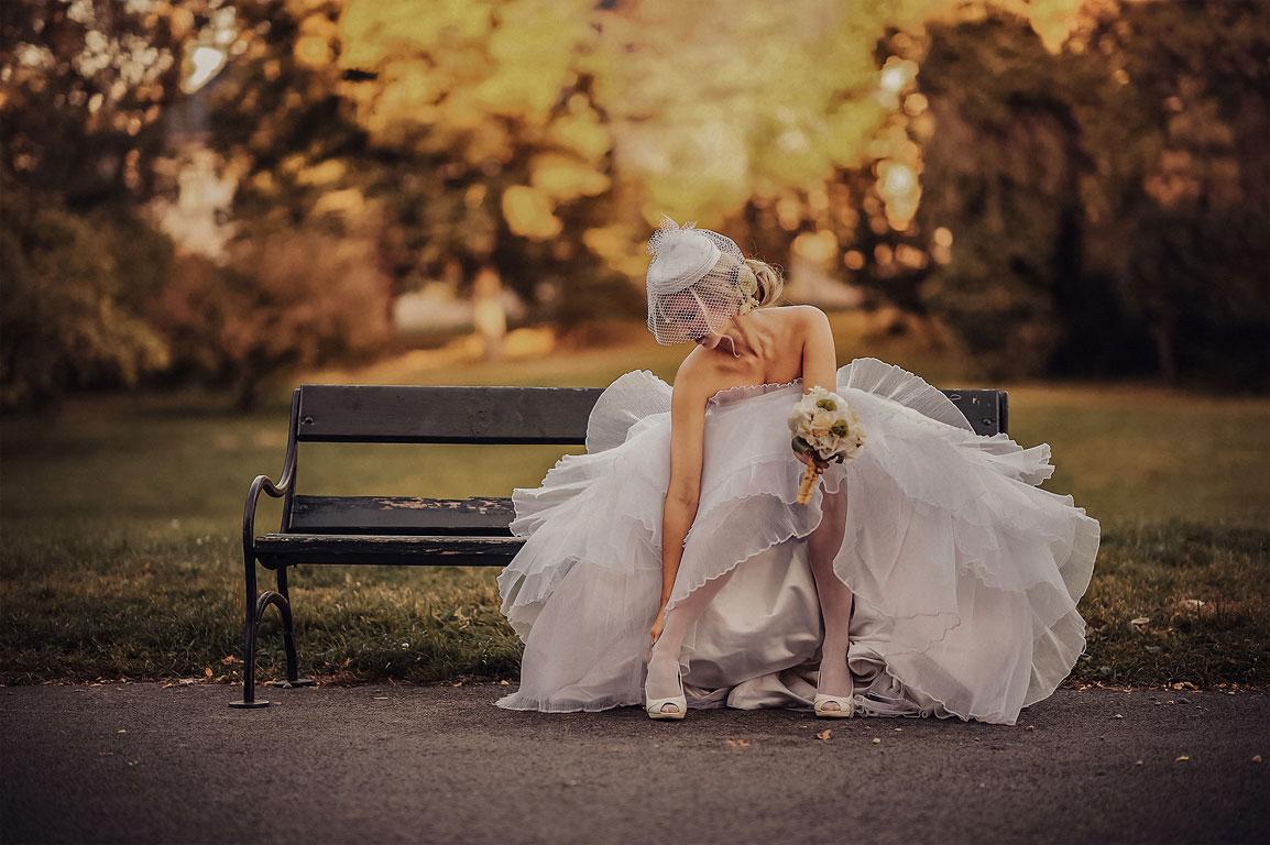 Nevěsta s kyticí v ruce sedí na lavičce a upravuje si boty