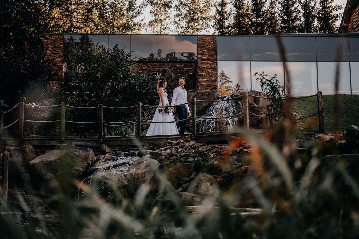 ženich s nevěstou se za ruce procházejí po mostu v Penzionu Jurášek v Beskydech