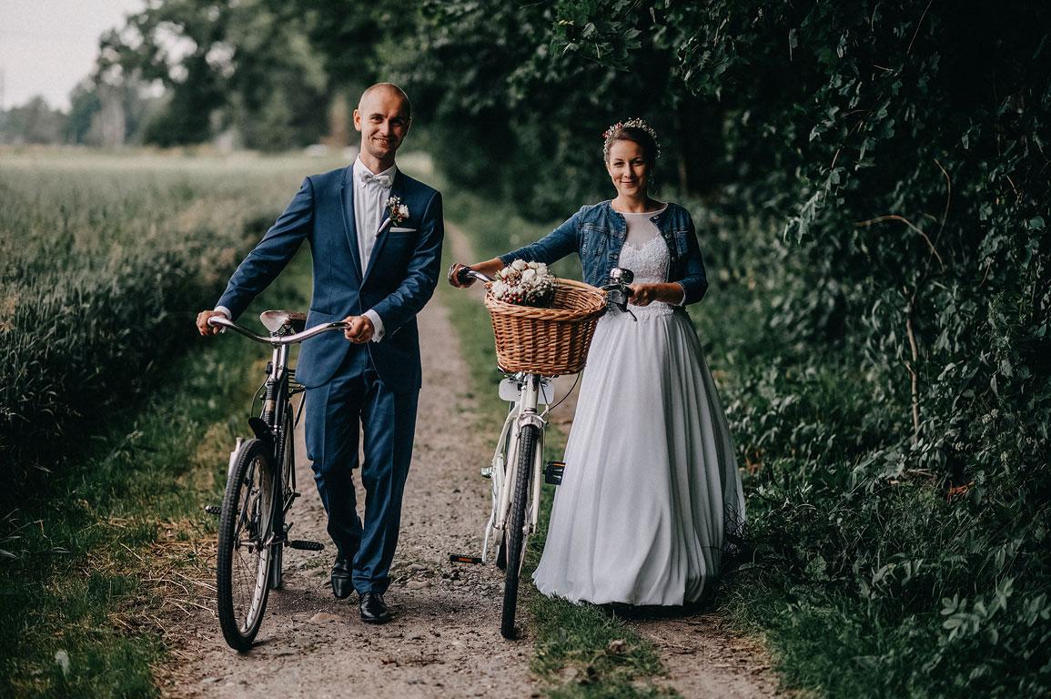 ženich s nevěstou vedou vedle sebe stará jízdní kola po polní cestě