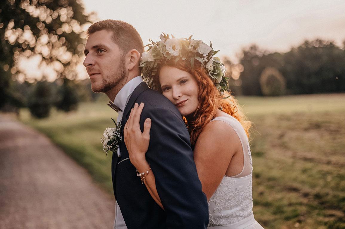 Nevěsta s věnečkem ve vlasech se opírá při západu slunce o ženicha
