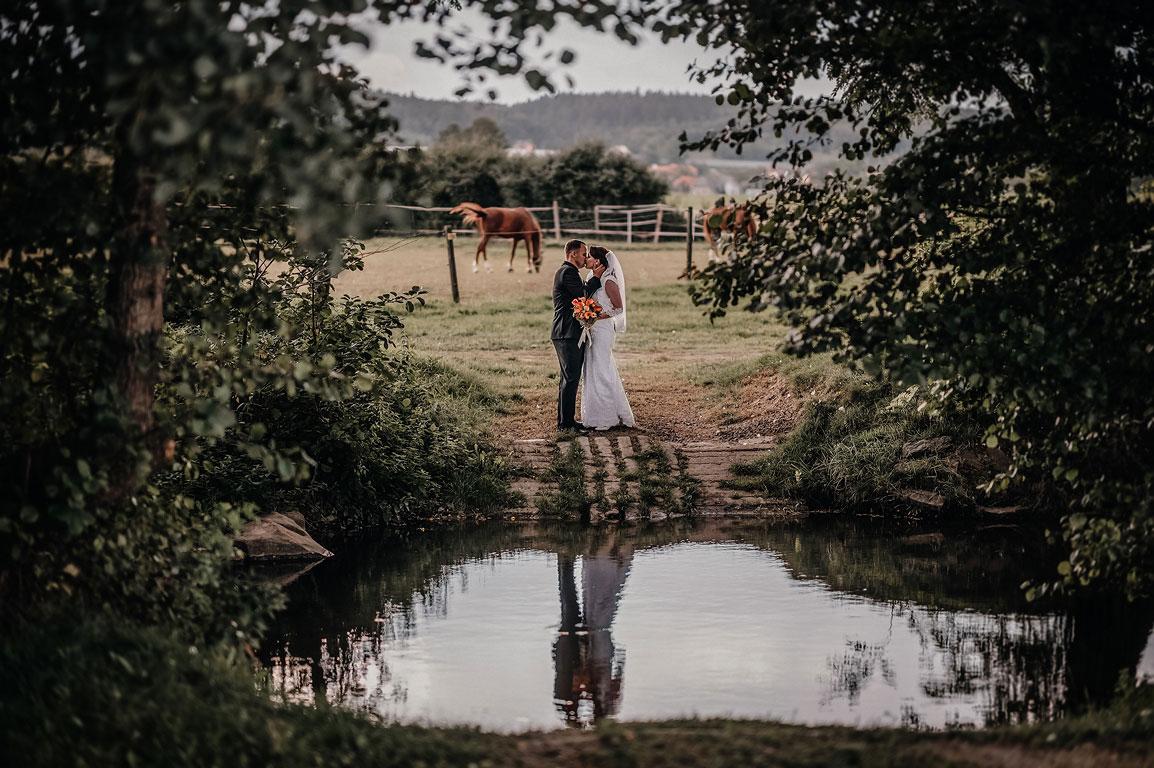 Nevěsta s ženichem se líbají v objetí před říčkou v Mlýně Vodníka Slámy, kde je jejich odraz ve vodě. V pozadí se pasou koně