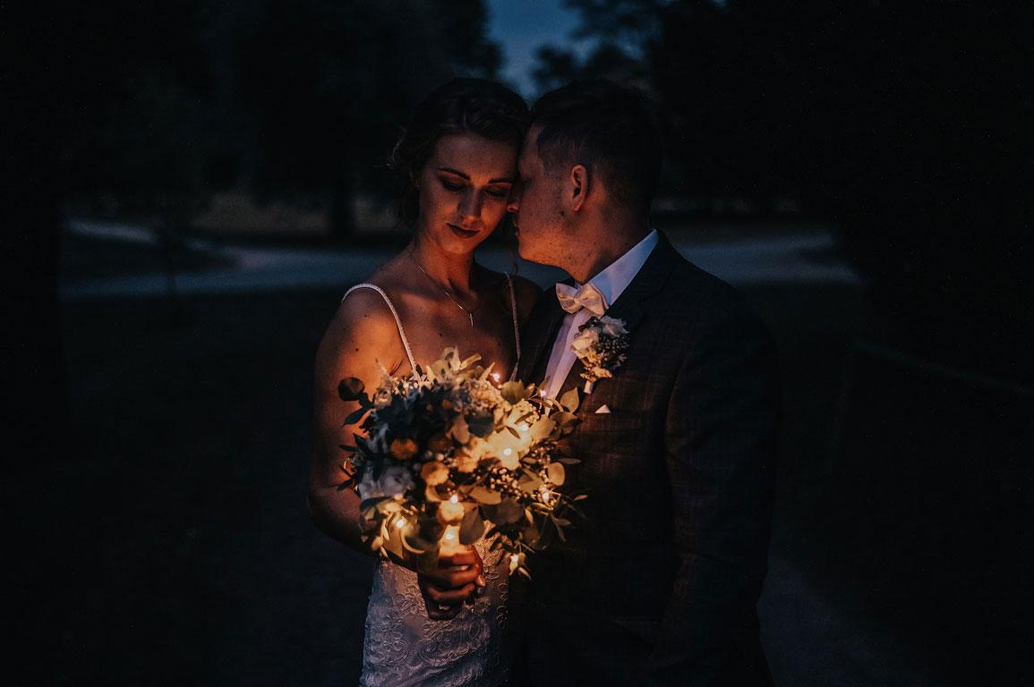 ženich s nevěstou opřeni k sobě čelem. Nevěsta drží v ruce svíticí svatební kytici.