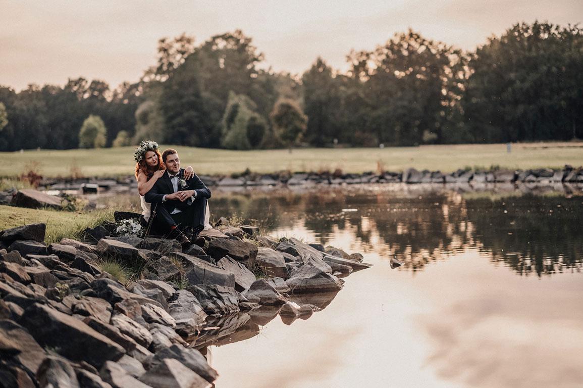 ženich s nevěstou sedí na kamenech na břehu jezírka v Zámeckém parku Kravaře
