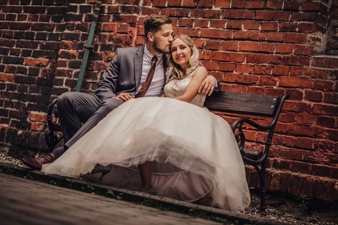 ženich s nevěstou sedí na lavičce na Landeku. Ženich dává nevěste pusu na čelo.