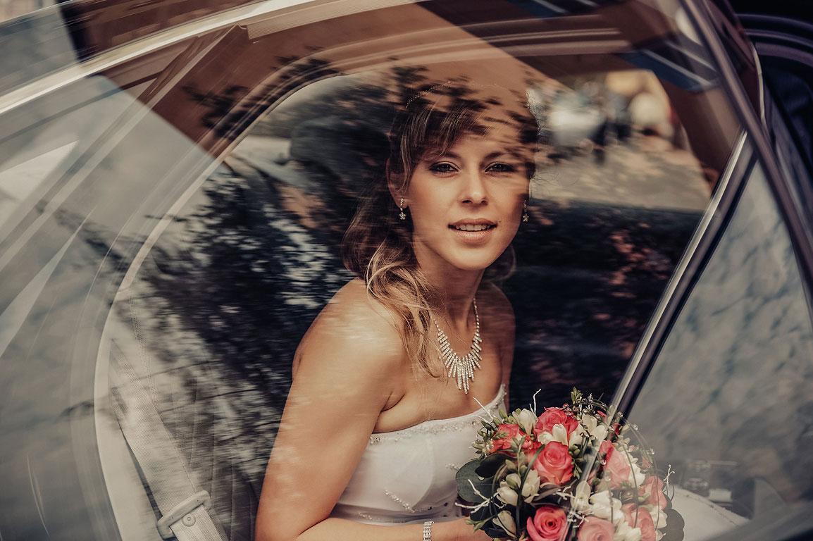 Pohled skrze okno auta na nevěstu držící v ruce svatební kytici