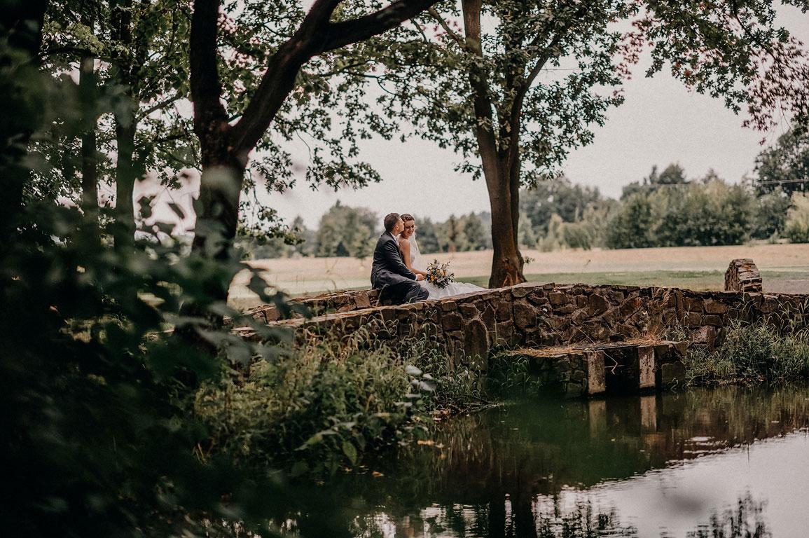 ženich dává polibek na čelo nevěstě sedící na mostě v Zámeckém parku Kravaře
