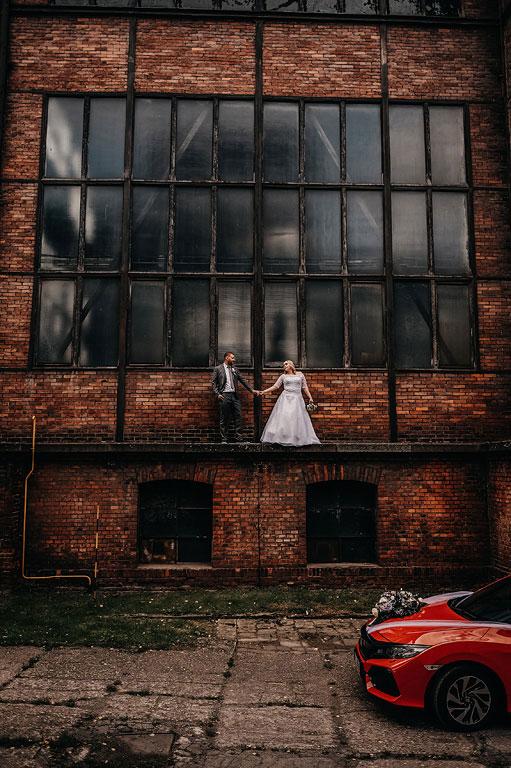 ženich s nevěstou stojí na římse v Dole Michal a drží se za ruce. Na cestě před nimi stojí červená svatební Honda Civic