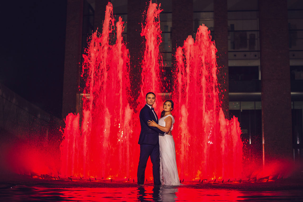 ženich s nevěstou stojí v noci v červeně osvětlené fontáně před knihovnou v Katowicích