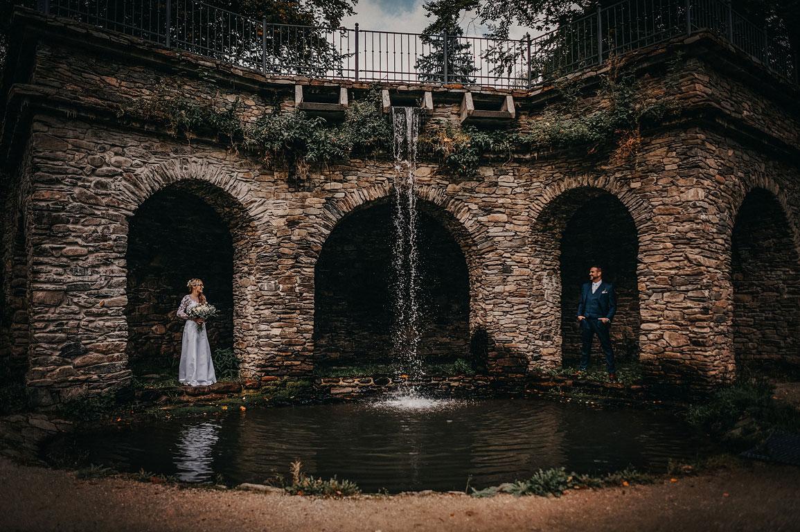 ženich s nevěstou na sebe koukají ve výklencích u malého vodopádu