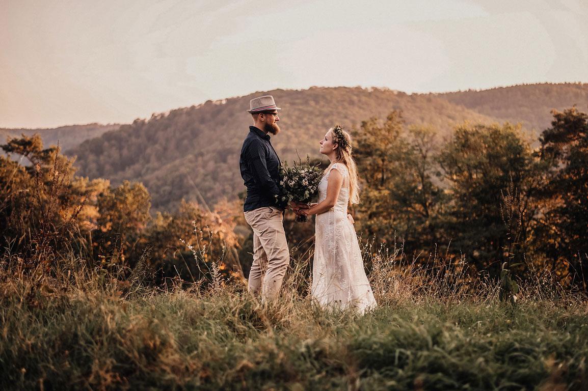 ženich s nevěstou stojí na kopci na louce a koukají zamilovaně na sebe. mezi sebou drží svatební kytici