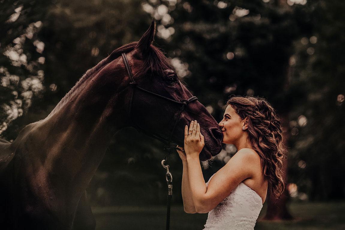 Nevěsta hladí koně a dává mu pusu na nozdry